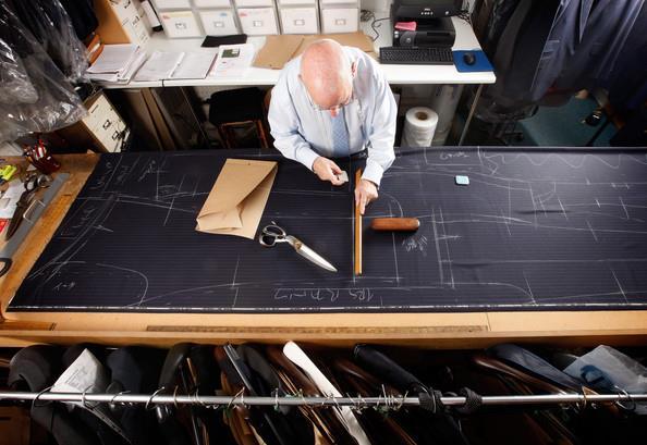 Nghệ nhân Peter O'Neil  (Gieves and Hawkes) đang cắt một bộ suit cho khách hàng đặt đồ bespoke (Ảnh: Dan Kitwood)