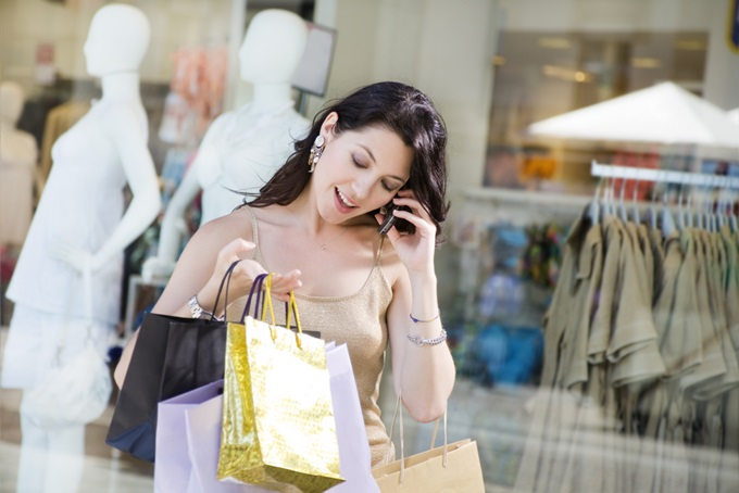 Mid-adult-Italian-woman-on-the-phone-and-holding-shopping-bags