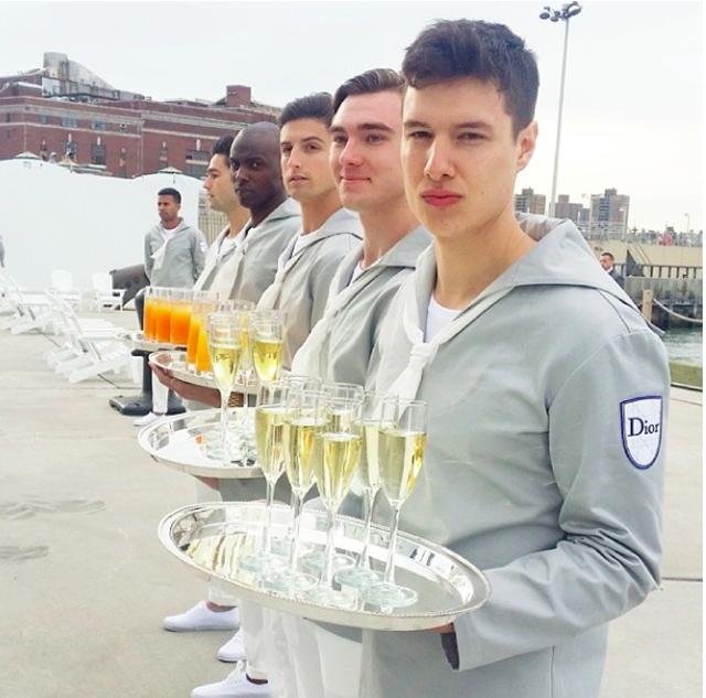Những chàng trai mặc đồ thủy thủ đứng phục vụ champagne