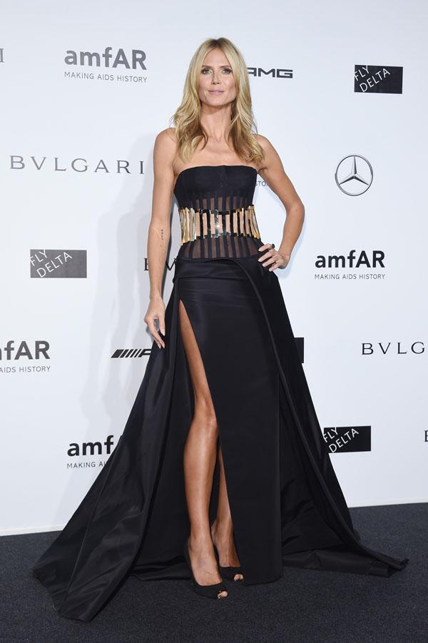 Siêu mẫu Heidi Klum xuất hiện cùng mẫu đầm quây đen, xẻ cao khoe chân dài đính hoạ tiết kim loại ở vòng eo, lấy từ BST Versace Atelier Thu Đông 2014