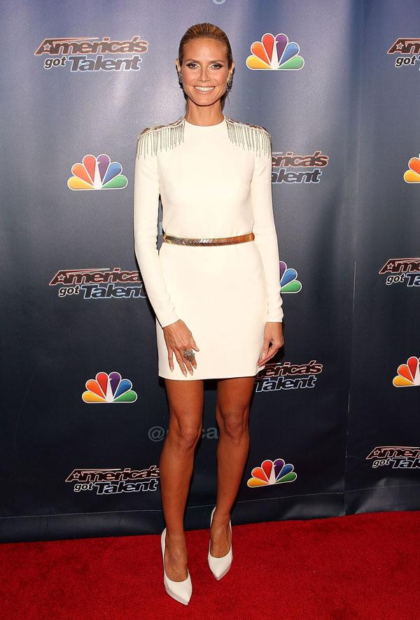 Sự tín nhiệm của siêu mẫu Heidi Klum với nhà mốt Versace được thể hiện qua việc lựa chọn mẫu đầm dài tay màu trắng với cầu vai nạm vàng, thuộc BST Versace Thu Đông 2014, khi tham dự sự kiện của chương trình America's Got Talent