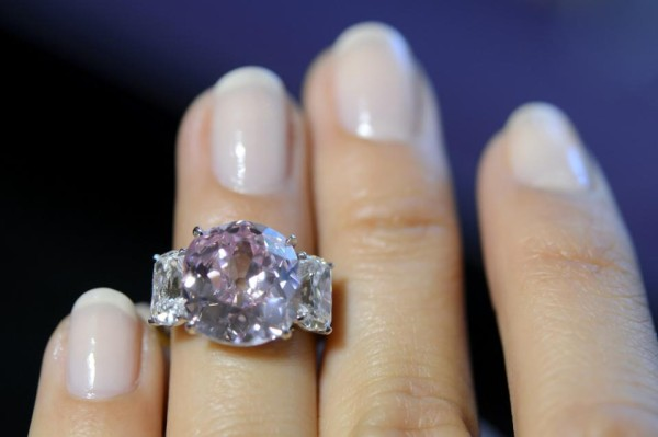 A Sotheby's employee shows ''the Historic Pink'', a ring with a fancy vivid pink diamond weighing 8.72 carats and with a classic non-modified cushion cut, which is estimated to sell between 14,000,000 to 18,000,000 US dollar, during a preview at the Sotheby's auction house in Geneva, Switzerland, Wednesday, May 6, 2015. The auction will take place in Geneva on May 12, 2015. (Martial Trezzini/Keystone via AP)