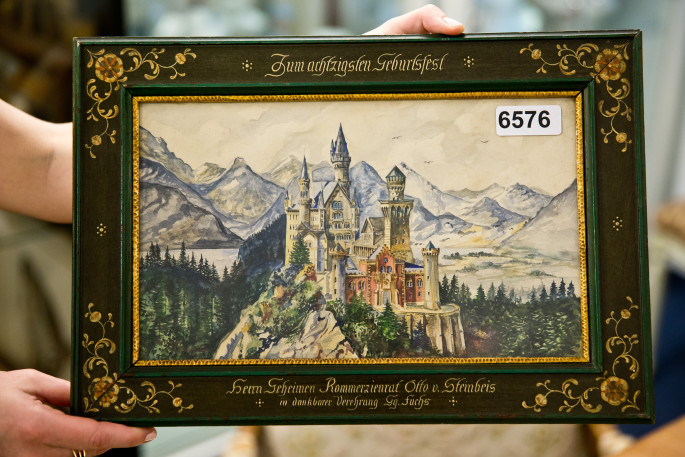 epa04794969 The frame of the watercolour painting 'Neuschwanstein', that is inscribed 'To the 80th birthday of Kommerzienrat (lit. councillor of commerce) Otto von Steinbeis', is on display at an auction house in Nuremberg, Germany, 12 June 2015. The painting is attributed to Adolf Hitler and will go under the hammer at the auction house Weidler on 20 June 2015.  EPA/DANIEL KARMANN