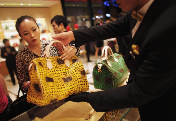 A woman shops in a Louis Vuitton store during Vogue's 4th Fashion's Night Out: Shopping Night with Celebrities in downtown Shanghai in this September 7, 2012 file photograph. Wealthy Chinese are likely to buy fewer luxury goods again this year after the steepest cut-back on spending in three years. Overall spending by wealthy Chinese fell by 15 percent and gift-giving fell by a quarter in 2013, the third consecutive year of decline, according to a survey by the Hurun Report.   REUTERS/Carlos Barria/Files   (CHINA - Tags: FASHION BUSINESS SOCIETY WEALTH)